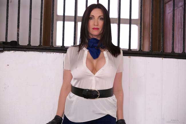 Miss Hybrid limbers up in the stables in boots and cords with her riding crop.
